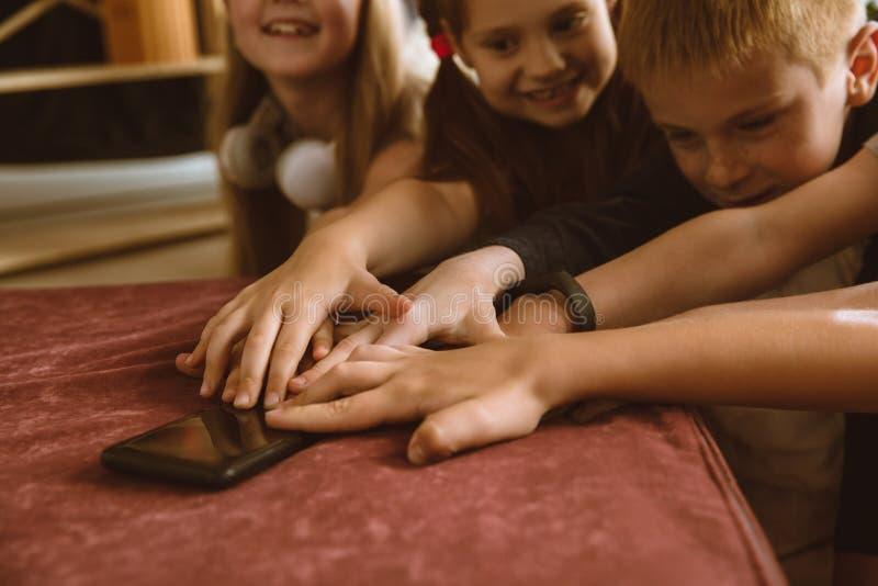 Wenig Jungen und Mädchen, die zu Hause verschiedene Geräte verwenden stockfotos