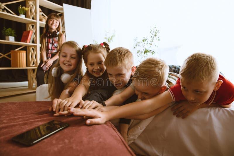 Wenig Jungen und Mädchen, die zu Hause verschiedene Geräte verwenden lizenzfreie stockbilder