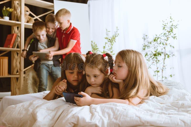 Wenig Jungen und Mädchen, die zu Hause verschiedene Geräte verwenden stockbild