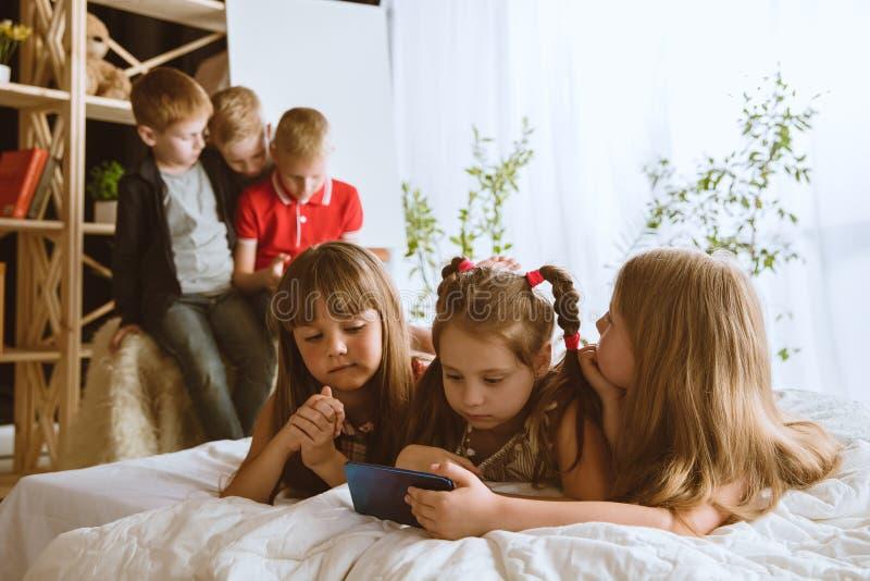 Wenig Jungen und Mädchen, die zu Hause verschiedene Geräte verwenden lizenzfreies stockbild