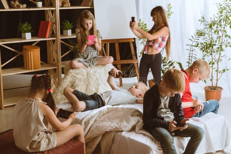 Wenig Jungen und Mädchen, die zu Hause verschiedene Geräte verwenden lizenzfreie stockfotos