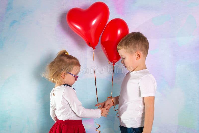 Wenig Jungen- und M?dchenkleinkinder mit roten Herzballonen Roter heart-shaped Schmucksachegeschenkkasten und eine rote Spule auf stockfotografie