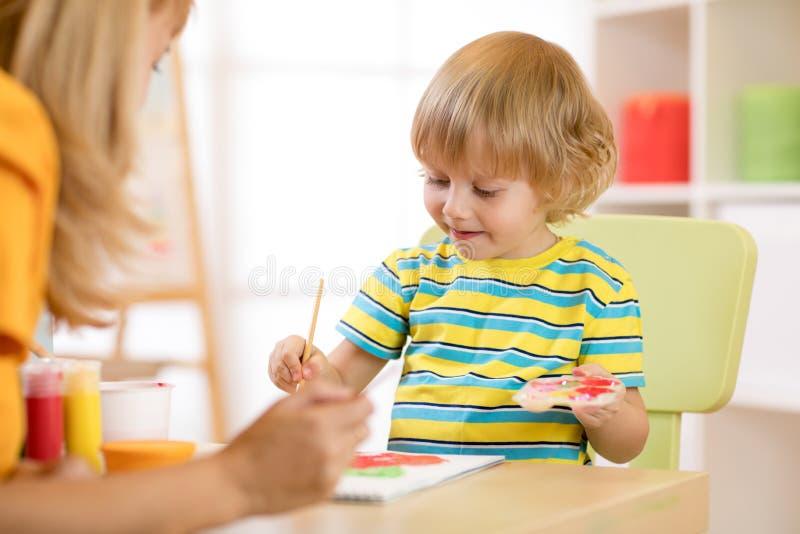 Wenig Jungenmalerei mit Lehrer im Klassenzimmer stockbilder
