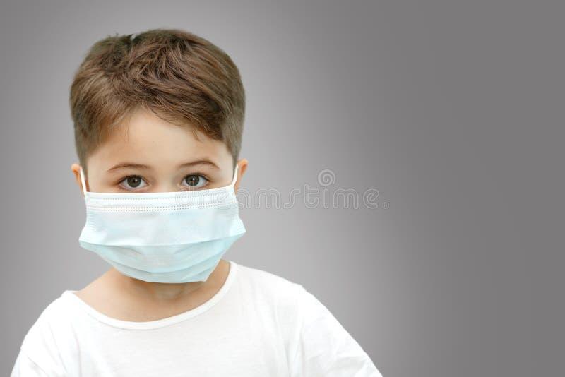 Wenig kaukasischer Junge in der medizinischen Maske auf lokalisiertem Hintergrund stockfoto