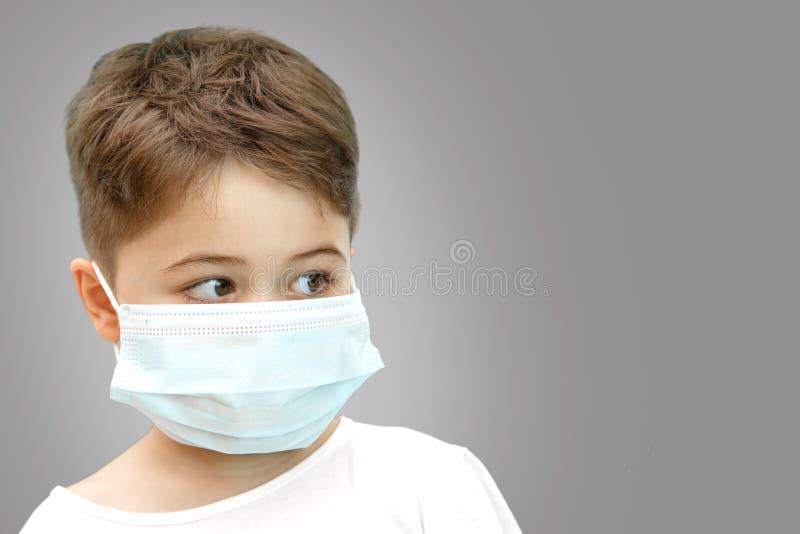 Wenig kaukasischer Junge in der medizinischen Maske auf lokalisiertem Hintergrund stockbild