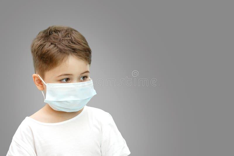 Wenig kaukasischer Junge in der medizinischen Maske auf lokalisiertem Hintergrund stockbilder