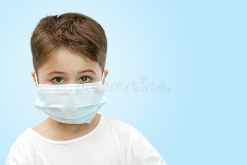 Wenig kaukasischer Junge in der medizinischen Maske auf lokalisiertem Hintergrund lizenzfreies stockfoto