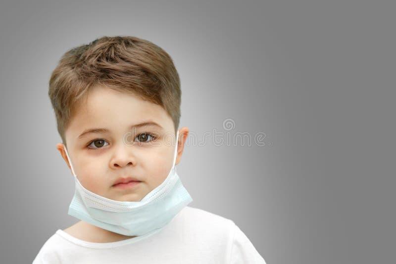 Wenig kaukasischer Junge in der medizinischen Maske auf lokalisiertem Hintergrund lizenzfreies stockbild