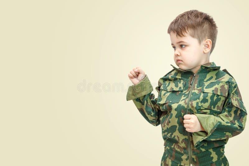 Wenig kaukasischer Junge in der Milit?rkleidung lokalisiert auf hellem Hintergrund lizenzfreie stockfotografie