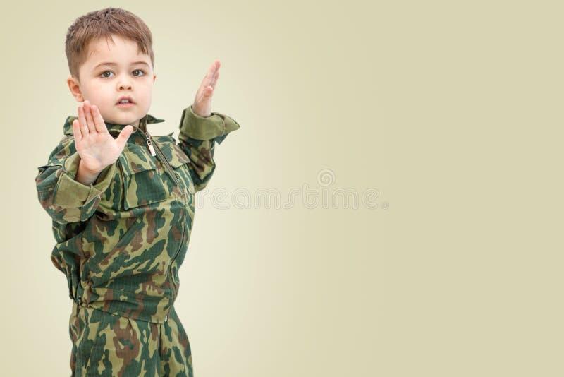 Wenig kaukasischer Junge in der Milit?rkleidung lokalisiert auf hellem Hintergrund lizenzfreies stockbild