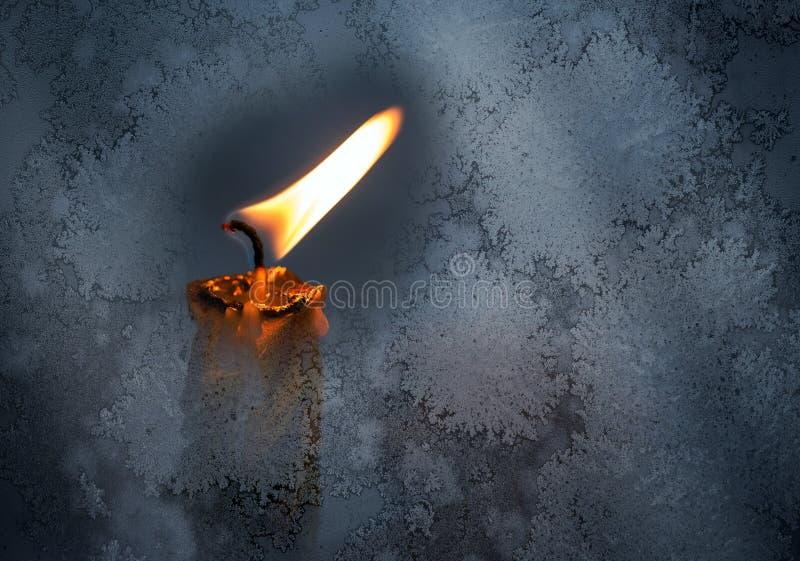 Wenig Kerzenflamme hinter gefrorenem Fensterglas lizenzfreies stockbild