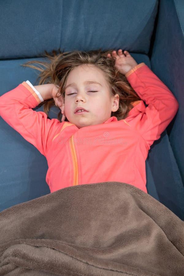 Wenig Kind, das auf blauem Sofa schläft stockbilder