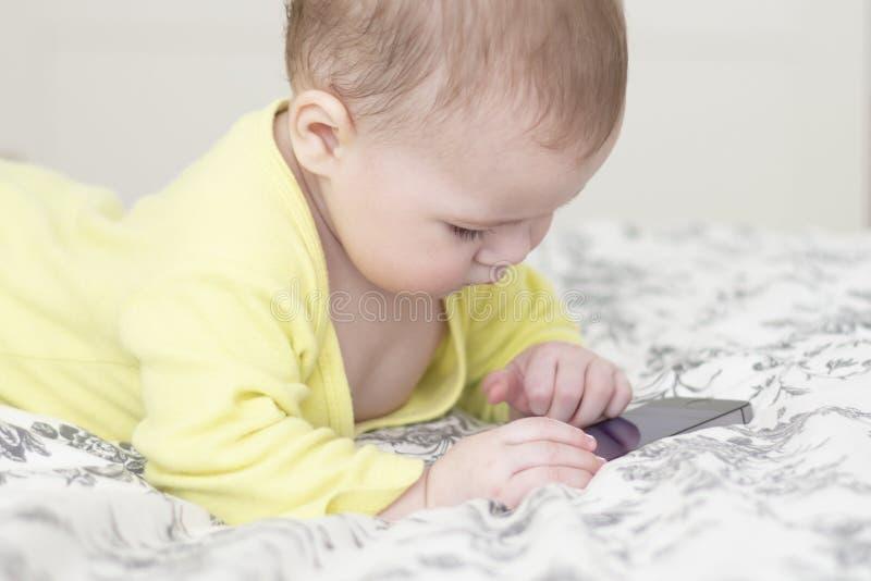 Wenig Kind mit einem Handy Baby 7 Monate, die an dem Smartphone interessiert werden, liegt auf dem Bett und stößt einen Finger am stockfotografie