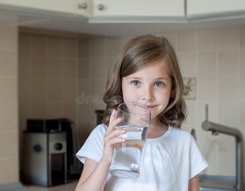 Wenig Kind trinkt Trinkwasser zu Hause, Abschluss oben Kaukasisches nettes Mädchen mit dem langen Haar hält ein Wasserglas in ihr stockbild