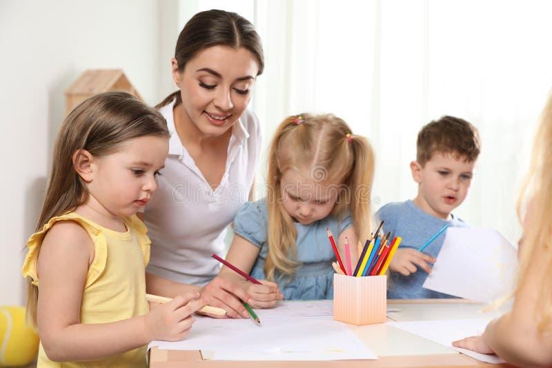 Wenig Kinder mit der Kindergärtnerin, die bei Tisch zeichnet Lernen und Spielen stockbilder