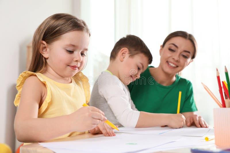 Wenig Kinder mit Kindergärtnerinzeichnung Lernen und Spielen lizenzfreie stockbilder