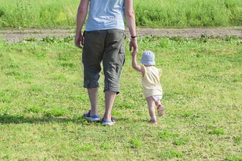 Wenig Kindereinjähriges Baby geht, die Hand des Vatis zu halten Der Vater geht mit dem Kind durch das grüne Gras Baby lernt t lizenzfreies stockbild