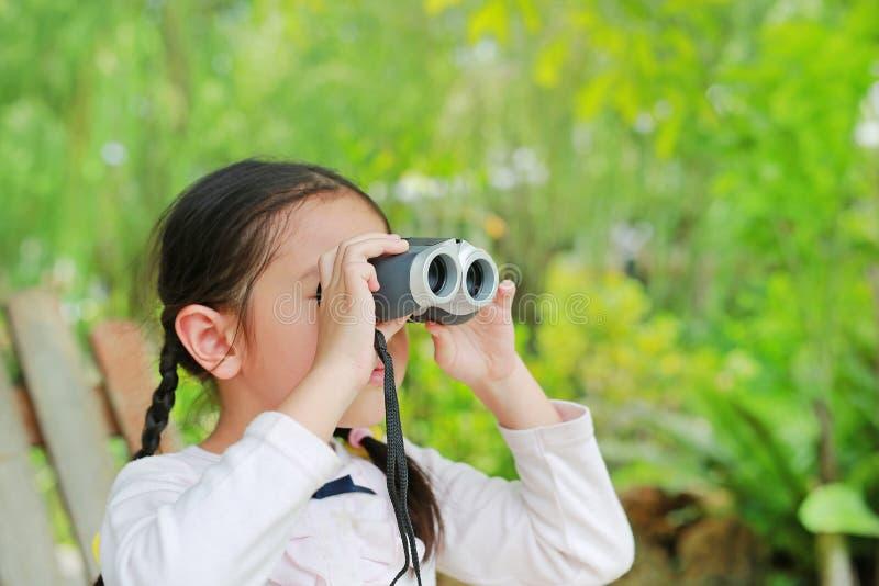 Wenig Kindermädchen auf einem Gebiet, das durch Ferngläser in der Natur im Freien schaut Erforschen Sie und wagen Sie Konzept lizenzfreies stockfoto