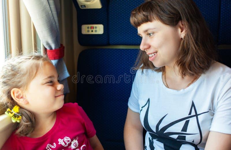 Wenig Kindermädchen und ihre Mutter, die durch das Fenster im Zug schauen lizenzfreies stockfoto