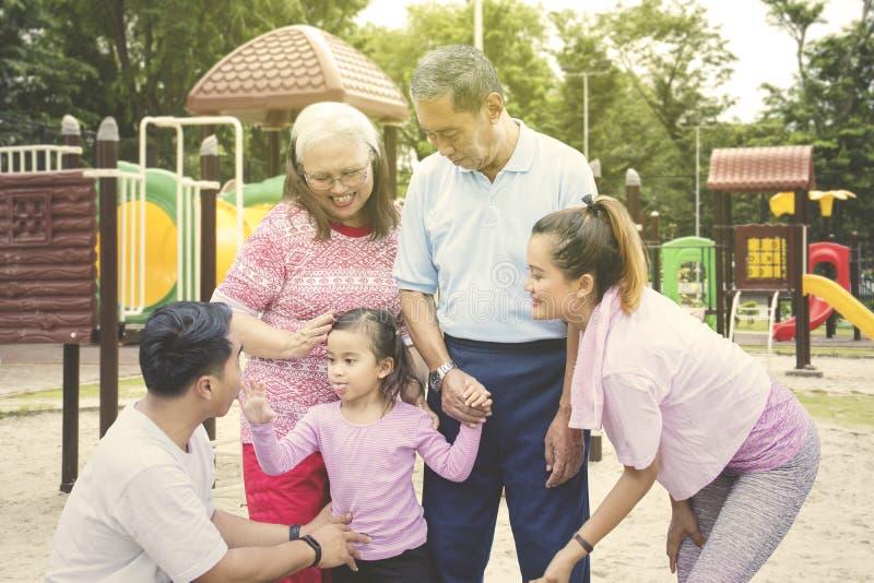 Wenig Kinderspiele mit ihrer Familie im Spielplatz lizenzfreies stockfoto