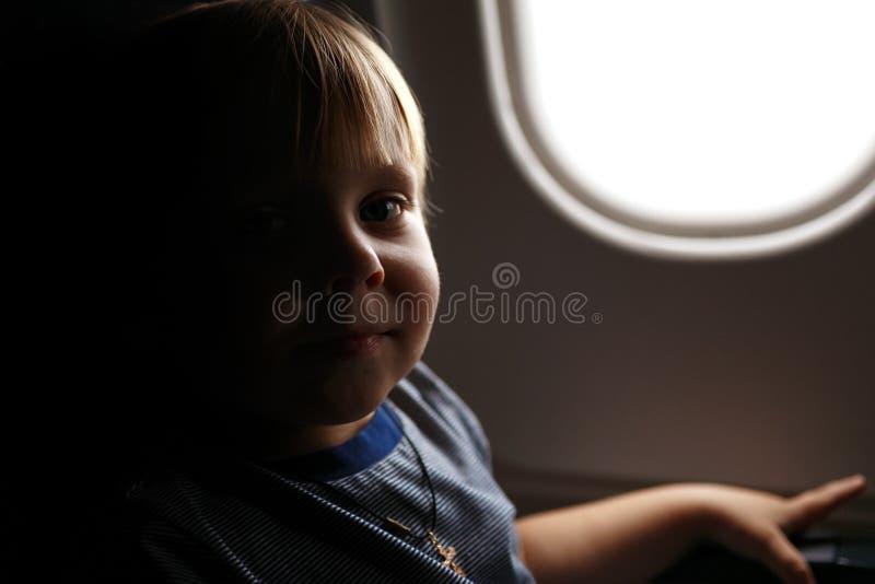Wenig Kleinkindjunge des blonden Haares, der in Flugzeug reist lizenzfreie stockfotos