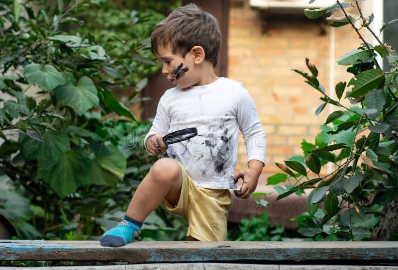 Wenig Kleinkindjunge mit schmutzigem Gesicht und schmutzigen der Kleidung, die durch eine Lupe auf Natur schaut stockfoto