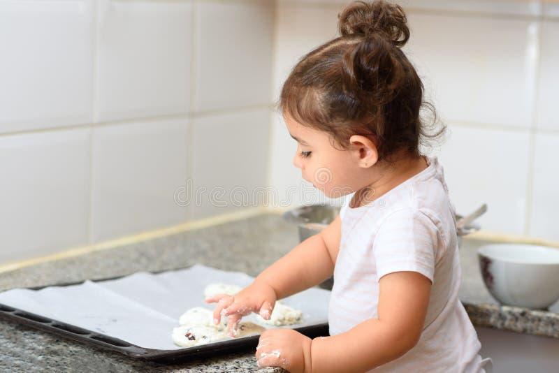 Wenig Kleinkindm?dchen, das Kuchenb?ckerei in der K?che macht stockfoto