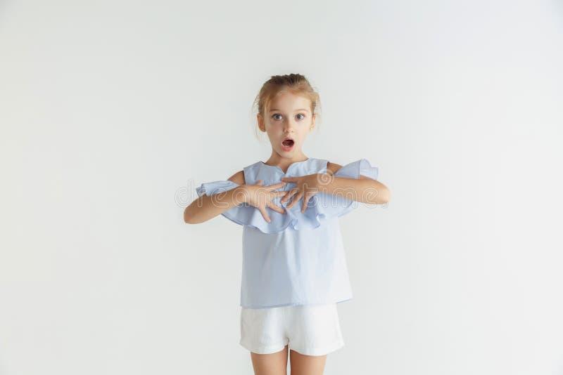 Wenig lächelndes Mädchen, das in der zufälligen Kleidung auf weißem Studiohintergrund aufwirft lizenzfreie stockfotografie