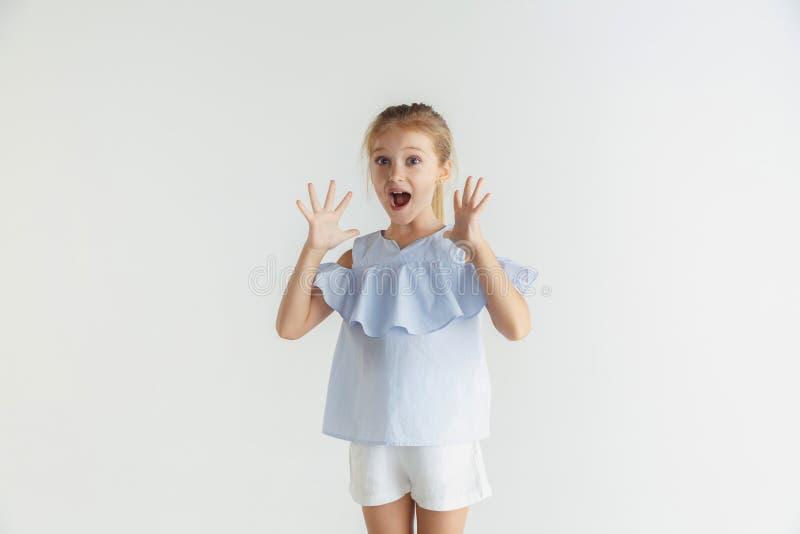 Wenig lächelndes Mädchen, das in der zufälligen Kleidung auf weißem Studiohintergrund aufwirft stockfoto