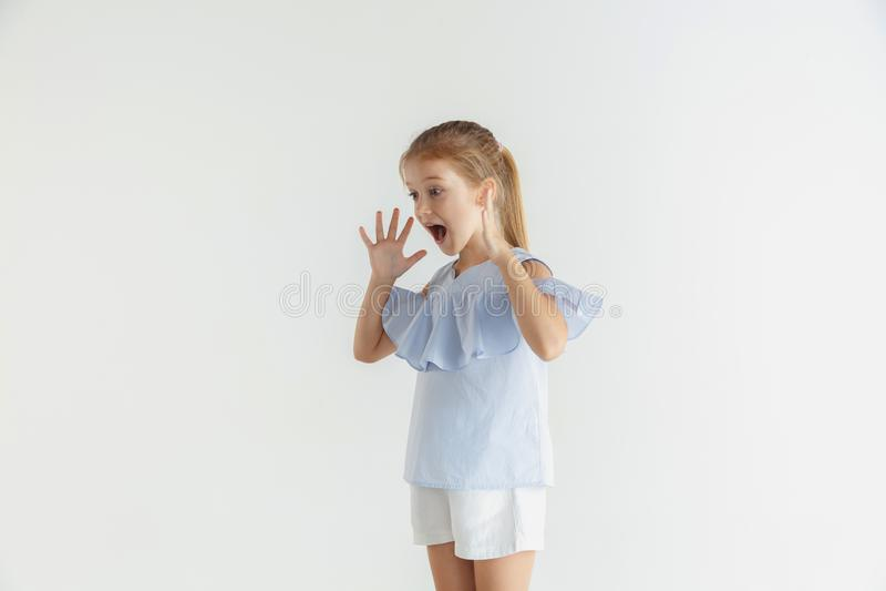 Wenig lächelndes Mädchen, das in der zufälligen Kleidung auf weißem Studiohintergrund aufwirft lizenzfreie stockfotos