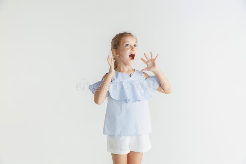 Wenig lächelndes Mädchen, das in der zufälligen Kleidung auf weißem Studiohintergrund aufwirft stockbild
