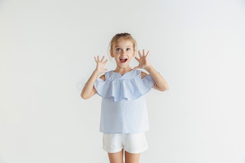 Wenig lächelndes Mädchen, das in der zufälligen Kleidung auf weißem Studiohintergrund aufwirft stockfotos