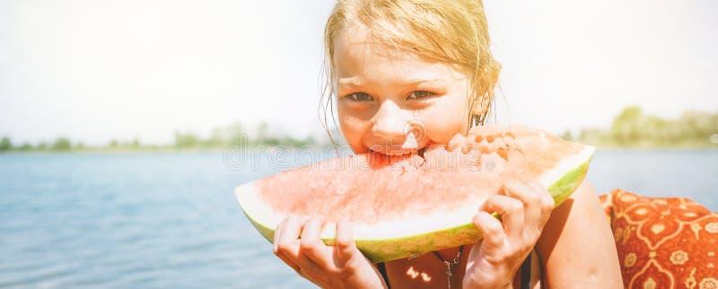 Wenig lächelndes Mädchen, das rotes Wassermelonenporträt auf dem Strand isst stockfoto