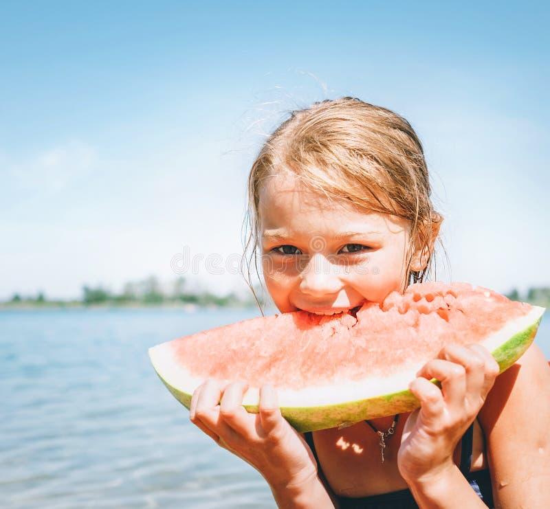 Wenig l?chelndes M?dchen, das rotes Wassermelonenportr?t auf dem Strand isst stockfotos
