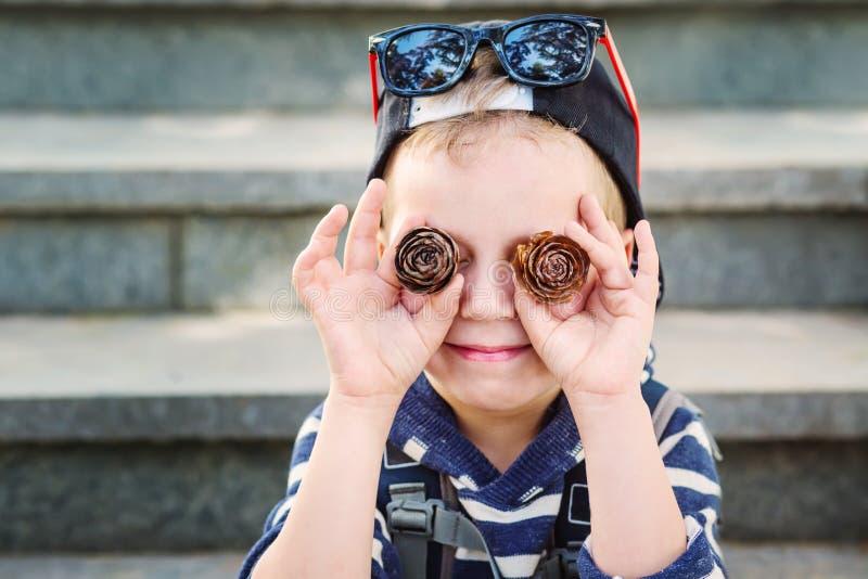 Wenig lustiger Junge, der mit Kiefernkegeln spielt lizenzfreie stockbilder