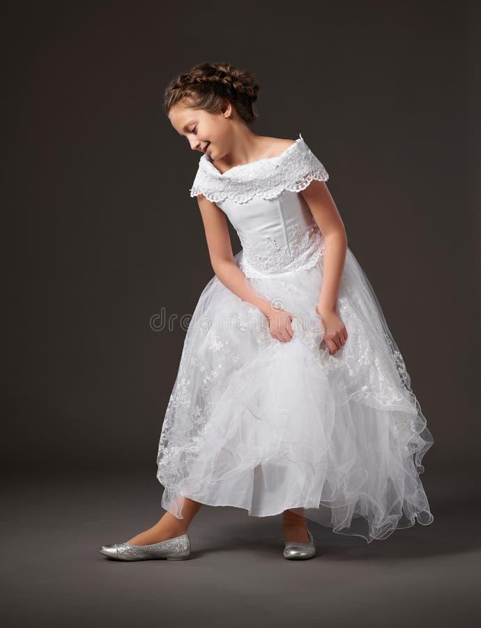 Wenig Mädchen wirft in einem weißen Ballkleid, dunkler Hintergrund auf stockbild