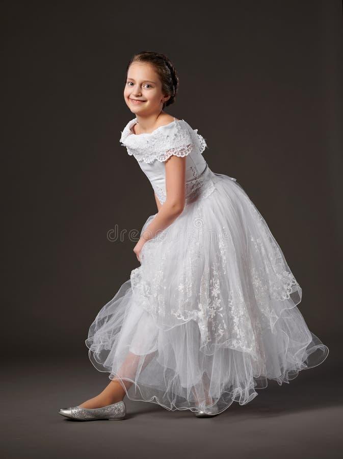 Wenig Mädchen wirft in einem weißen Ballkleid, dunkler Hintergrund auf lizenzfreies stockfoto