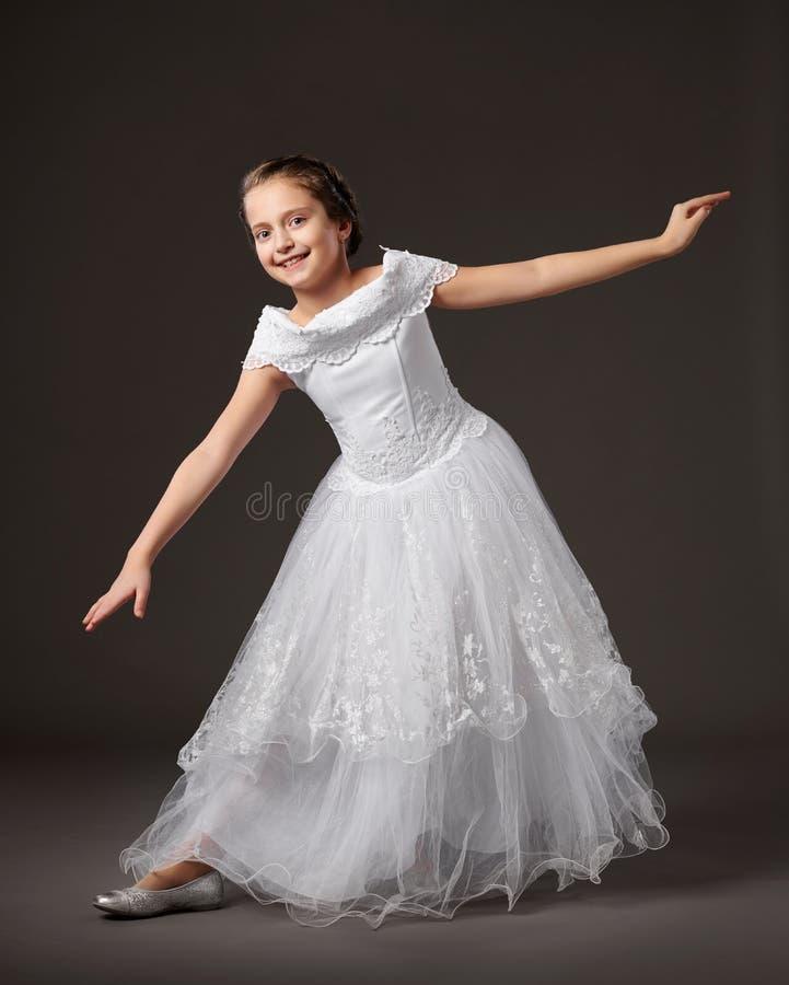 Wenig Mädchen wirft in einem weißen Ballkleid, dunkler Hintergrund auf lizenzfreie stockfotos