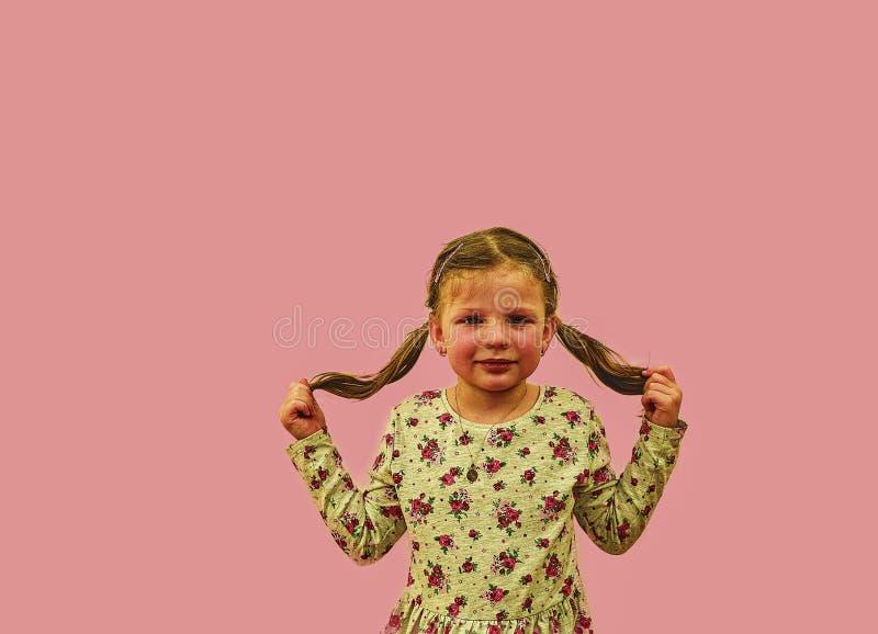 Wenig Mädchen auf buntem Hintergrund Kopieren Sie Platz Junges Mädchen trägt geblümtes Kleid Mädchen mit Seitenpferdeschwänzen So stockbilder