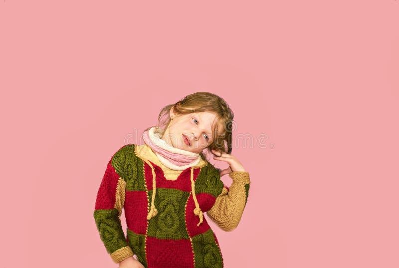 Wenig Mädchen auf buntem Hintergrund Kopieren Sie Platz Junges Mädchen trägt Strickjacke Weicher rosafarbener Hintergrund stockfoto