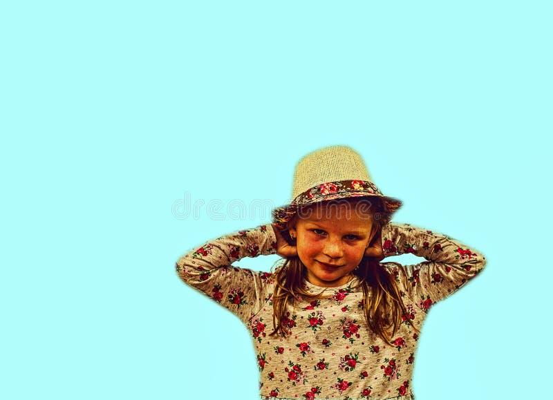 Wenig Mädchen auf buntem Hintergrund Kopieren Sie Platz Junges Mädchen trägt Strohhut und geblümtes Kleid Weich Blau stockbild