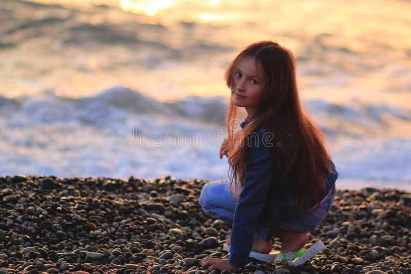 Wenig Mädchen auf dem Strand, Sonnenuntergang, langes Haar stockbild