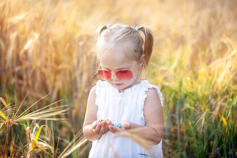 Wenig Mädchen, das auf dem sonnigen Sommergebiet spielt Baby im weißen Kleid und in der Sonnenbrille stockfotos