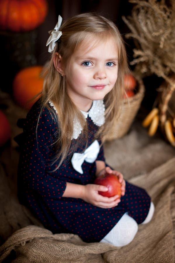 Wenig Mädchen, das einen Apfel in einem Herbstinnenraum hält lizenzfreie stockfotografie