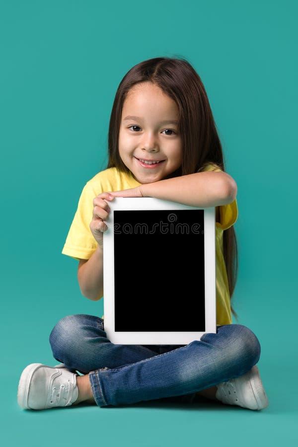 Wenig Mädchen, das einen leeren Tablet-Computer hält lizenzfreies stockfoto