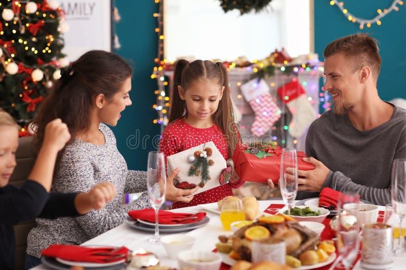 Wenig Mädchen, das Geschenke von ihren Eltern während des Weihnachtsessens empfängt stockbild