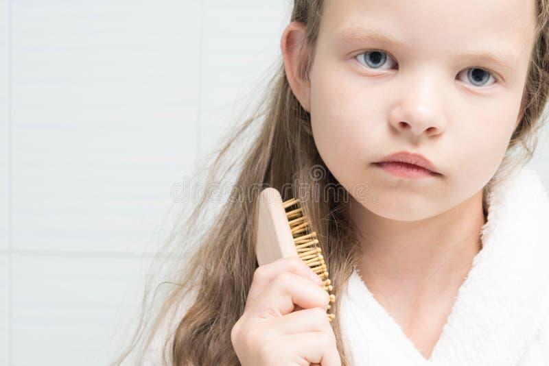 Wenig Mädchen, das Haar mit einem hölzernen Kamm, Porträt kämmt stockfotos