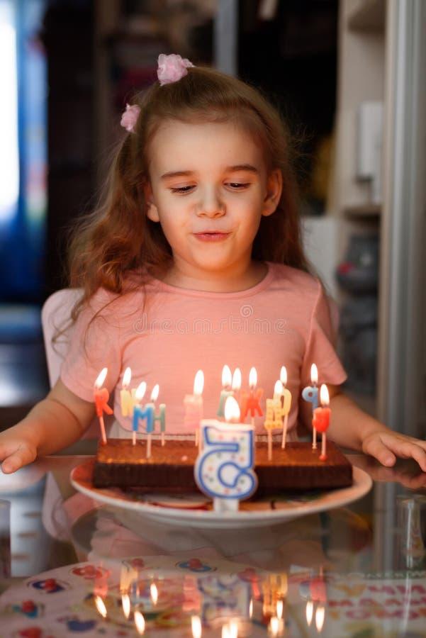 Wenig Mädchen, das heraus Kerzen auf einem Geburtstagskuchen auf ihrem Geburtstagskopienraum durchbrennt lizenzfreie stockbilder