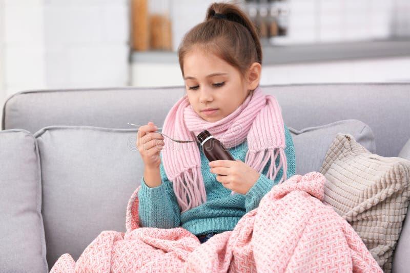 Wenig Mädchen, das Hustensirup auf Sofa nimmt lizenzfreie stockfotografie