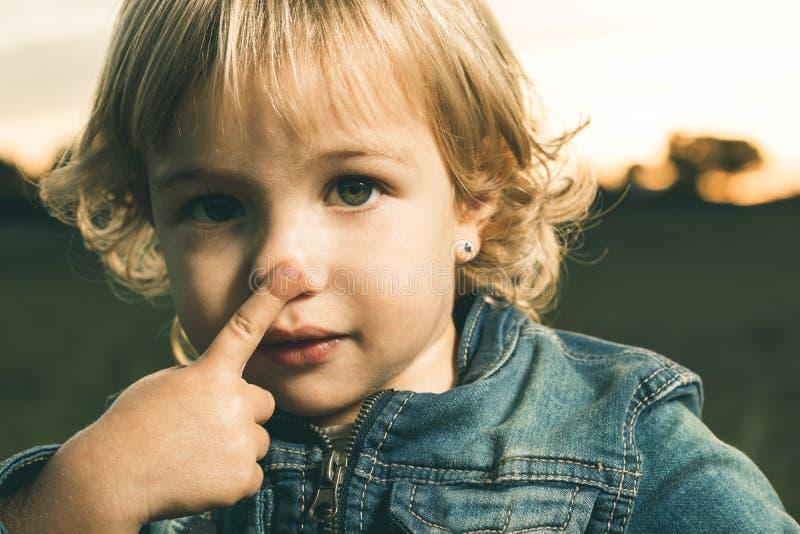 Wenig Mädchen, das ihre Nase mit einem Finger berührt stockfoto